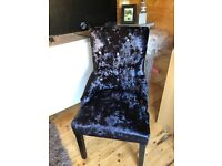 Black suede chair studded with knocker ring on back