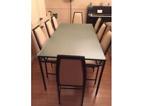 Glass-topped dining table, black metal frame. 8 chairs with cream leather seats and backs.
