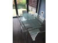 Glass dining table and 6 chairs. Table has chrome frame, chairs are white & chrome