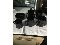 Black mugs with milk and sugar bowl