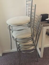 Four Cream and Chrome dining room chairs.