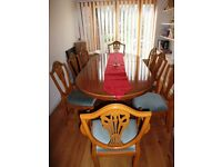 Classic English dining table with matching carver and dining chairs.