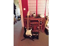 Encore eletric gutair with a bass amp, it has all leads and a stand.
