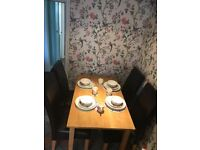 Very good condition light oak dining table and four brown leatherette chairs