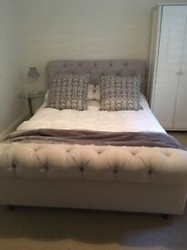 A beautiful sleigh bed in grey linen