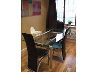 Large extendable glass dining table and 6 leather high backed chairs