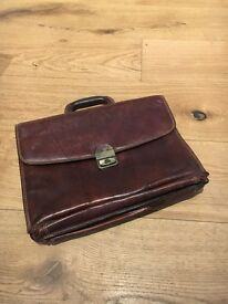 Brown leather briefcase with several compartments and pockets