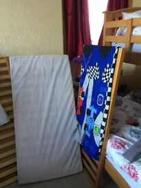 large cot bed with mattress and bedding