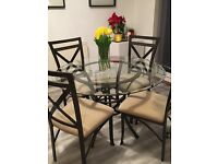 👀🍴Round glass dining table with 4 fabric seat chairs. Dark metal base with design. COLLECT NOW!!