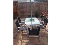 Glass top garden table with 6 grey chairs