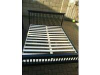 Black wooden king size bed with mattress
