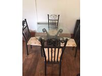 wrought iron effect glass table and 4 chairs