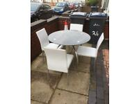 Lovely round glass dining table with white chairs