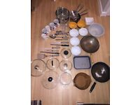 Mix random used kitchen utensils pots pans bowls knifes spoons spatulas cups mugs glasses sivves