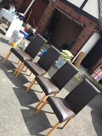 4 good condition brown chairs for a table.