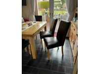 A set of six matching dining room chairs. Wooden frame with leather style finish