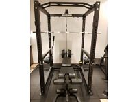 Power cage/squat rack with cable attachment. T bar row, bench (extension/curl), weights, mats, bars