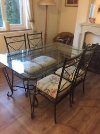 Dinning table and 6 chairs, glass top, cast iron frame,