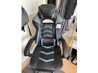 Office/Gaming chair with footrest still has tags attached, super comfy, recliner and swivel.