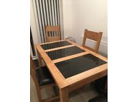 Wooden table with black marble inserts ,4 wooden chairs with padded leather seating good condition