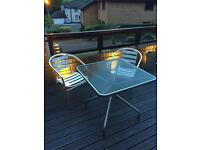 Outdoor table and two metal chairs