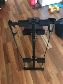 Incline bench for sit-ups and elastic chords for mild resistance training