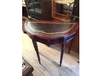 Half moon table with deep red/ brownish leather insert . In good condition. Reproduction .
