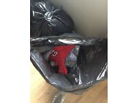 Black bags filled with clothes for boy from 0-9 months