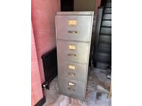 Stripped four drawer metal filing cabinet with casters