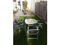 Garden table and chairs. glass top. metal grey chairs