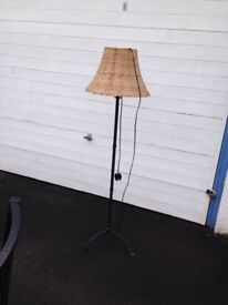 Standing lamp . Black metal pole and stand , wicker lamp shade .