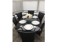 Beautiful Glass and Chrome table complete with 6 Black and leather chairs