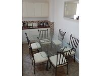 Glass topped dining table with 6 chairs