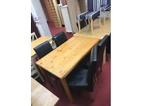 Solid Pine table Oak effect and 4 skirted black leather chairs