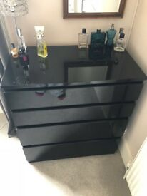 Shiny black chest of drawers and bedside table