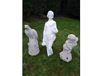 3 x stone statues, one of which is a water fountain.