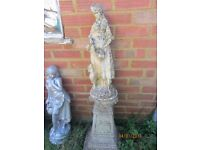 Stone heavy garden statue of girl on plinth weathered