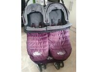 Baby Jogger City Mini Double Purple, with raincover, bumper bar and 2 purple cosy footmuffs.