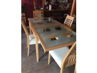 Light oak glass top extending table, 4 chairs and matching sideboard
