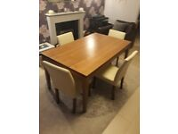 Walnut effect dining table and 4 cream cream chairs.