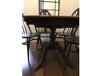 Ercol extending oval dining table with six swan back chairs finished in fruitwood colour(dark)