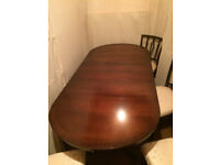 large extending dining table and four chairs.
