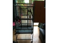 Parrot cage with perches and bowls and nesting box.