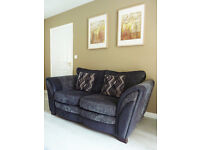 STYLISH Charcol grey two seater sofa with leather trim and patterned cushions.