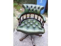 A green leather captain's style desk chair.