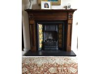 Open gas fire with flue and wooden surround.