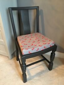 Dark grey chair with flamingo design seat