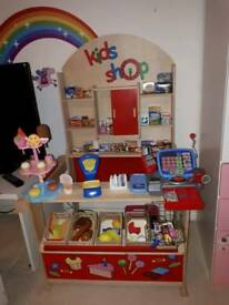 Kids play shop with food baskets and till