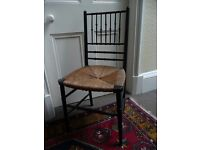 six chairs of ebonised wood with rush seating