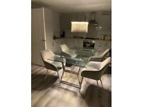 Glass dinning table and 4 grey suede chairs